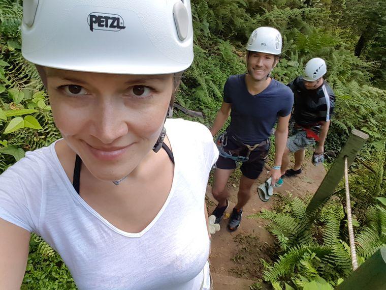 Ausgestattet mit Klettergurten, Helmen und Handschuhen geht es im Gänsemarsch durch den Regenwald.