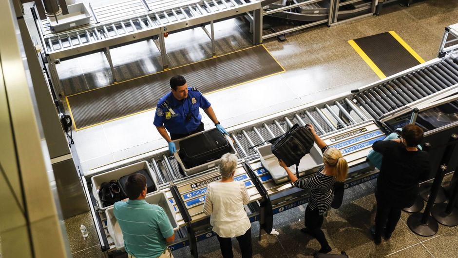 Passagiere legen ihr Handgepäck auf das Band der Sicherheitskontrolle durch die TSA am Flughafen Minneapolis/St. Paul International Airport.