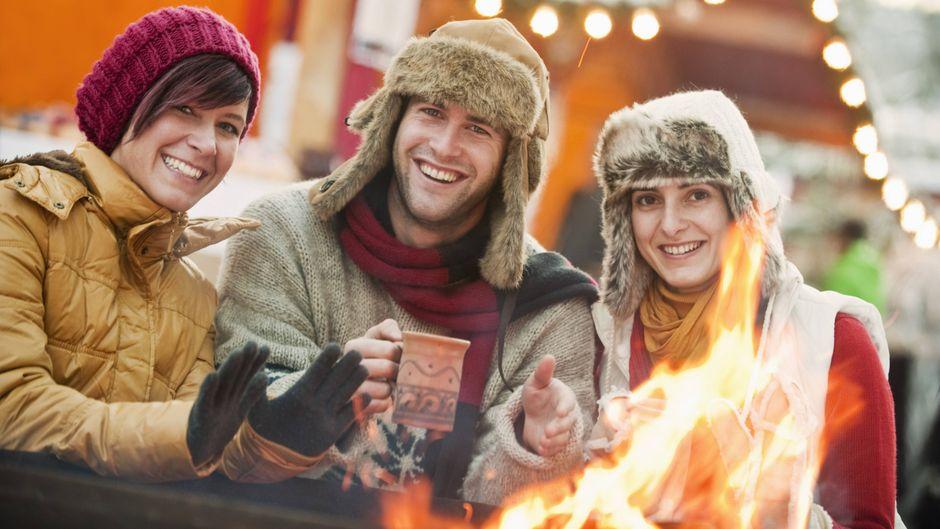 Ein Mann und zwei Frauen trinken auf einem Weihnachtsmarkt in Salzburg gemeinsam Glühwein.