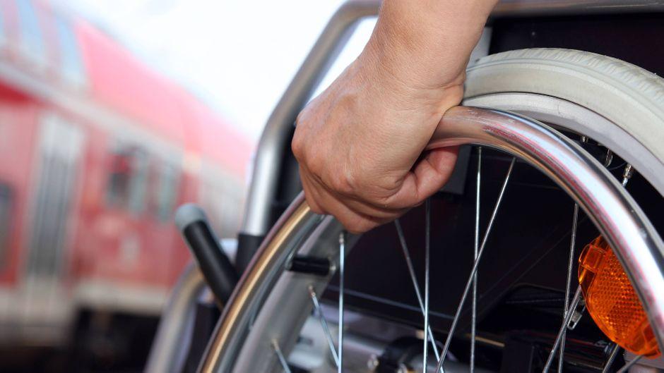 Ein Rollstuhlfahrer wartet am Gleis auf den Zug.
