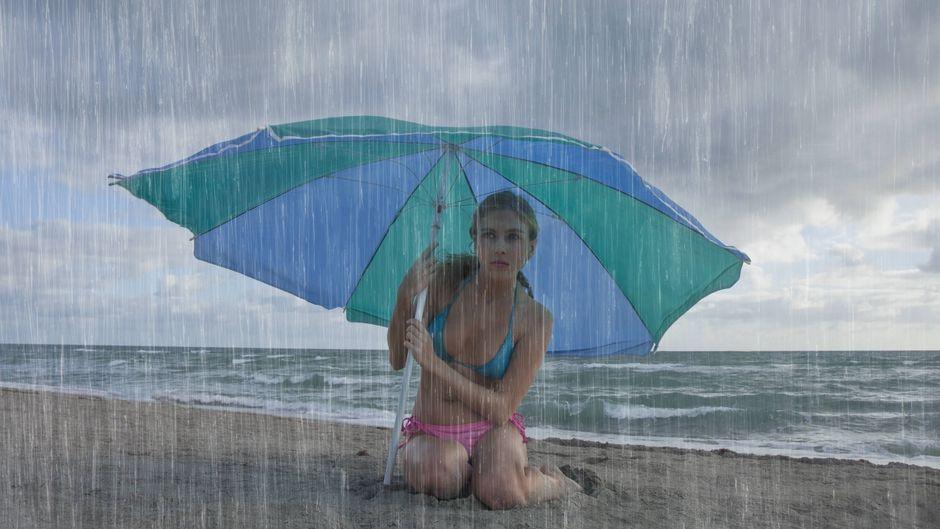 Frau sitzt bei Regen am Strand unter einem Sonnenschirm
