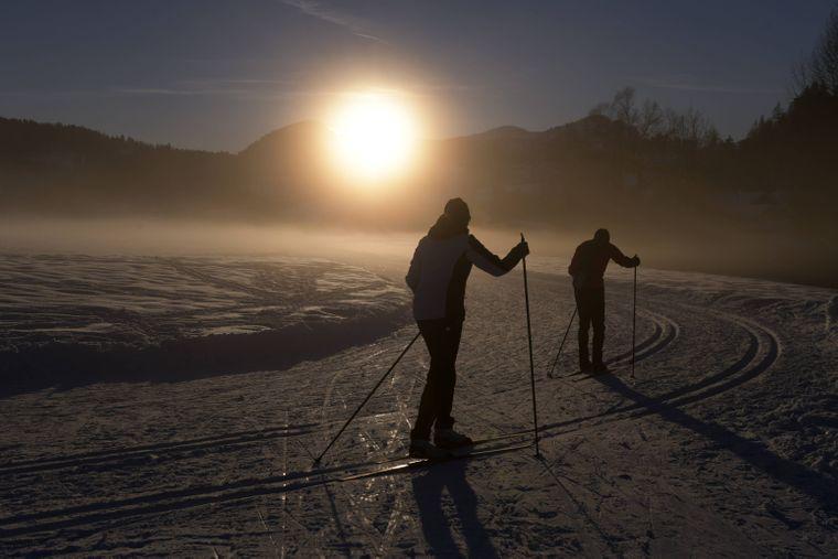 Nebel und Abendsonne senken sich auf die Schneedecke und die Langlaufloipe.