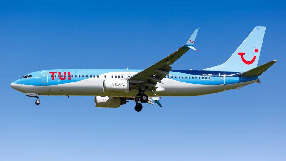 Eine Boeing 737 von Tui Airways fliegt vor blauem Himmel.