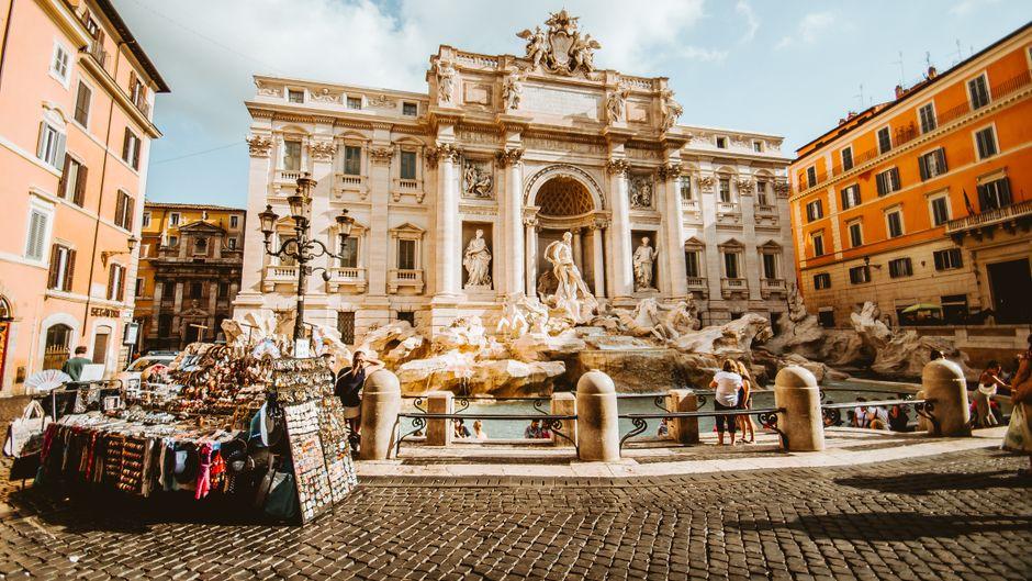 Touristen und ein Souvenirstand stehen vor dem Trevi-Brunnen in Rom.