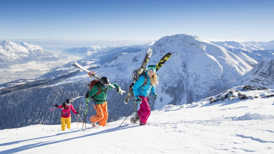 Skifahrer beim Aufstieg mit Blick ins Inntal und Innsbruck im Skigebiet Axamer Lizum in Österreich