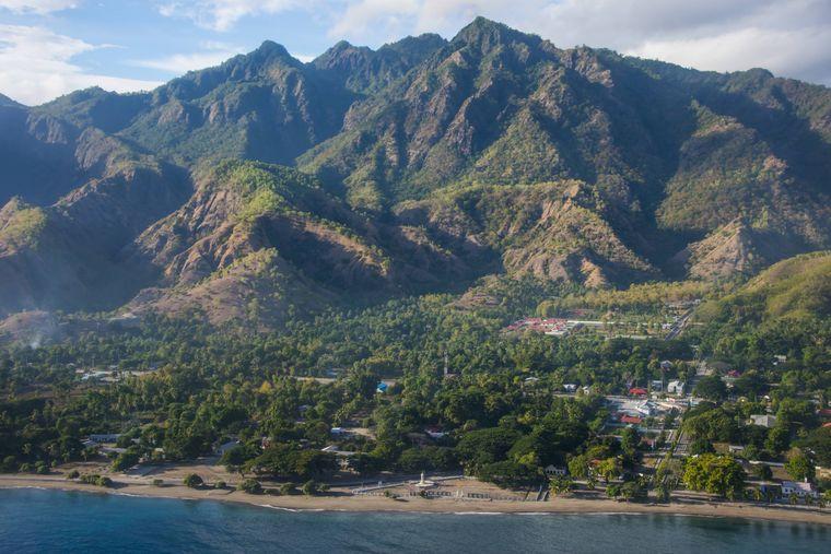 Blick auf die Küste von Osttimor mit einem Strand und den Bergen im Hintergrund.