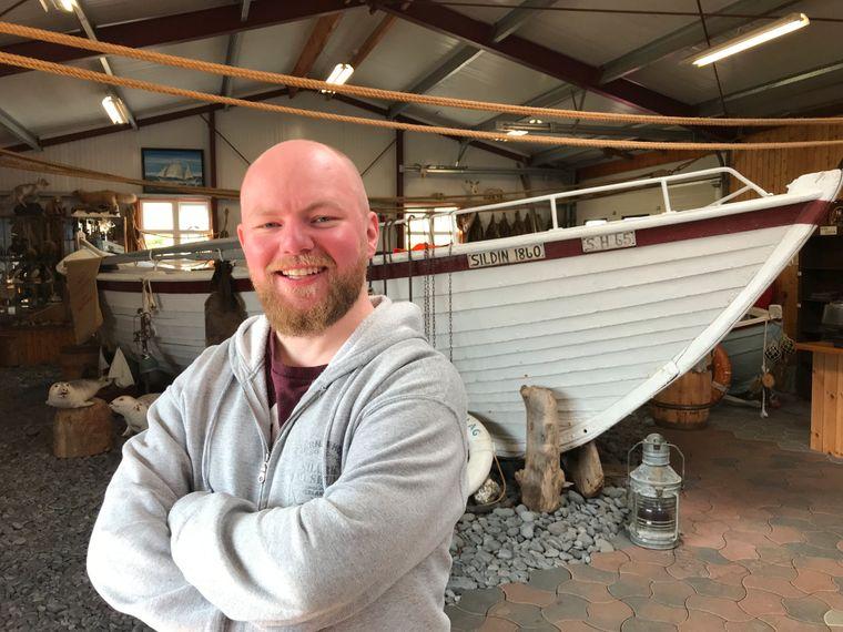 """Kristian Hildibrandsson stellt Reisenden im Bjarnarhöfn-Hai-Museum das älteste Boot Islands, die """"Sildin"""" vor."""