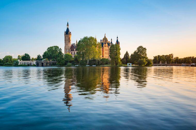 Das Schweriner Schloss spiegelt sich im Schweriner See bei Abendlicht. An diesem Anblick können sich auch Stand-up-Paddler erfreuen.