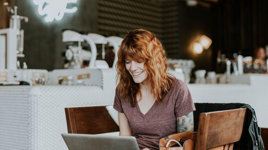 Frau in einem Kaffe sitzt lächelnd vor ihrem Laptop.