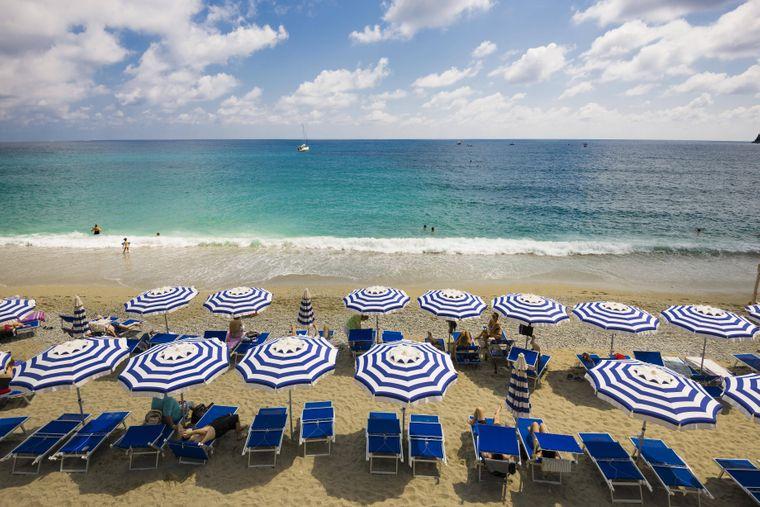 """Bunte Sonnenschirme am Sandstrand von Monterosso al Mare. In der Region Ligurien wurden 2021 Badeorte mit der """"Blauen Flagge"""" ausgezeichnet."""
