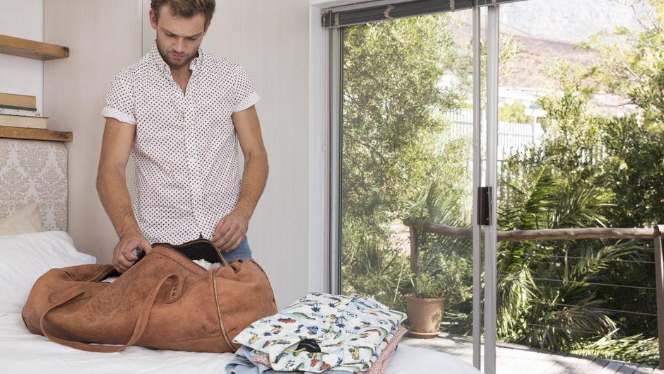 Ein Mann packt in seinem Hotezimmer seine Tasche.