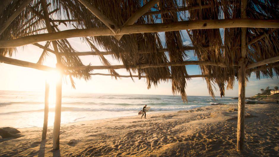 Surfer geht vom Meer an den Strand