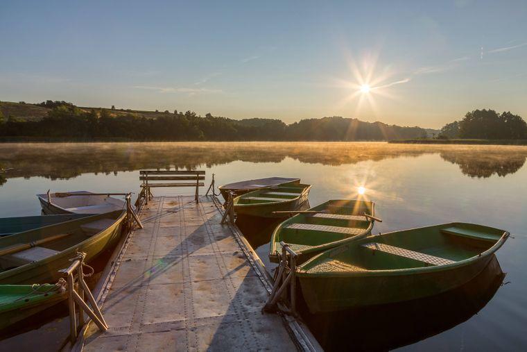Sonnenaufgang mit Ruderbooten an einem Bootssteg am Mellensee.