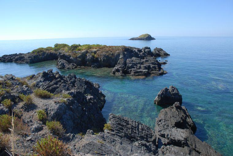 Ein Ort der Kontraste: das schimmernd grün-blaue Wasser am schwarzen Sandstrand des Naturparks Illicini ist ein beliebter Ort für Urlauber.