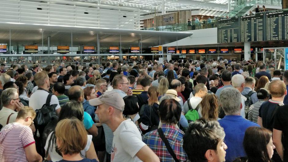 Hunderte Fluggäste stehen eng zusammen in der Wartehalle am Flughafen München. Das Terminal 2 wurde komplett geräumt.
