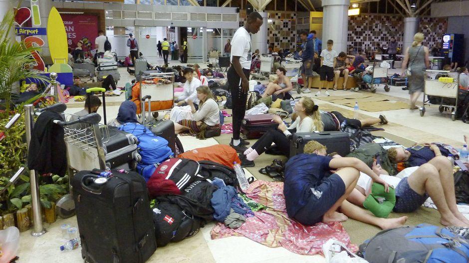 Touristen harren in der Lobby des Internationalen Flughafens von Lombok aus.