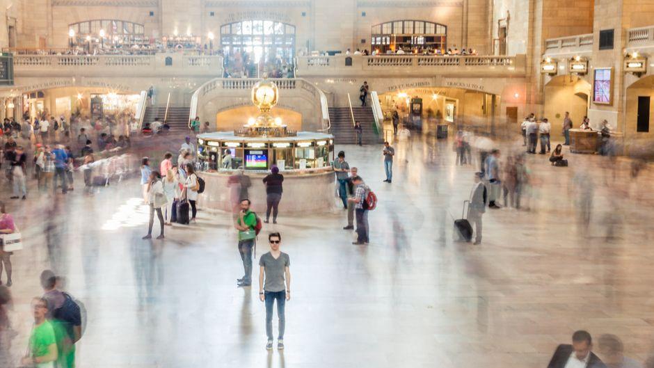 Ein junger Mann steht umgeben von Menschen alleine in der New York Central Station
