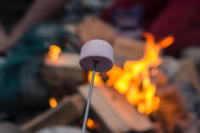 Marshmallows werden über einem Lagerfeuer geröstet.