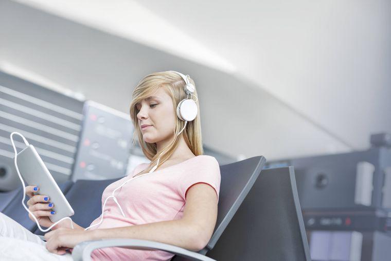 Das Mädchen nutzt ihr Tablet am Flughafen.