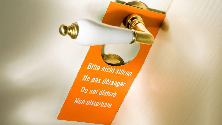 """Schild """"Bitte nicht stören"""" an einer weißen Hotelzimmertür mit Messingtürgriff."""