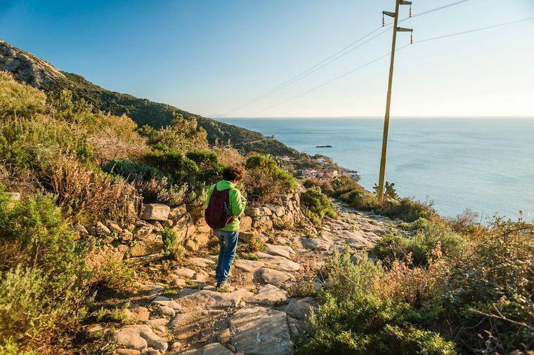 Eine Frau geht auf einem Wanderweg mit Meerblick bei Pomonte am Fuße des Monte Capanne auf Elba.