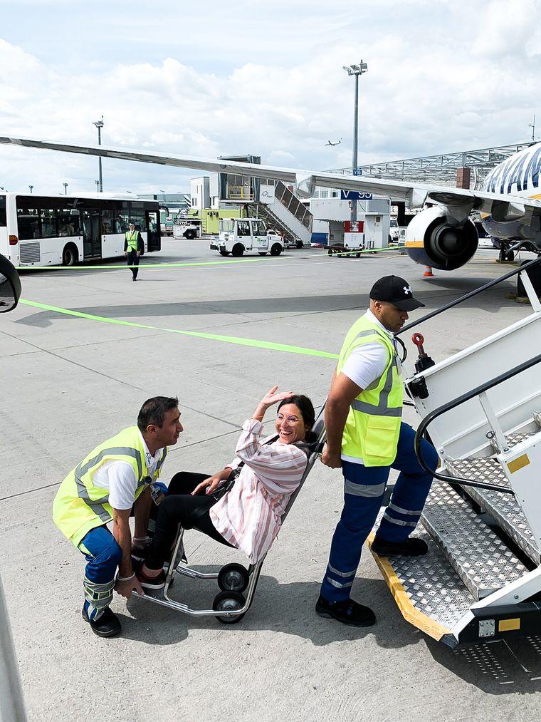Hier wird Kim beim Einsteigen in den Flieger geholfen.