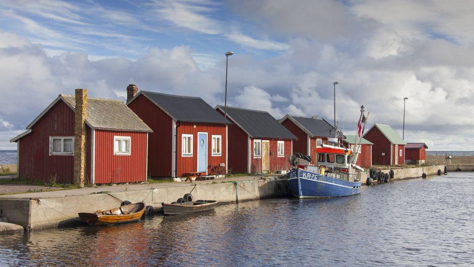 Rot-weiße Fischerhäuser in einem Hafen in Öland in Schweden