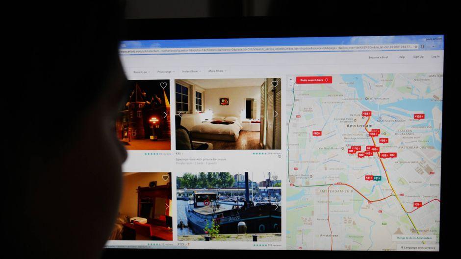Eine Frau sitzt vor dem Bildschirm und sucht nach Airbnb-Unterkünften.