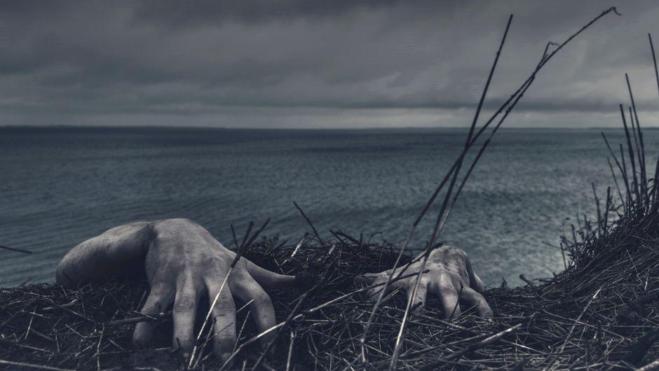 Dreckige Hände krallen sich an den Dünen fest.