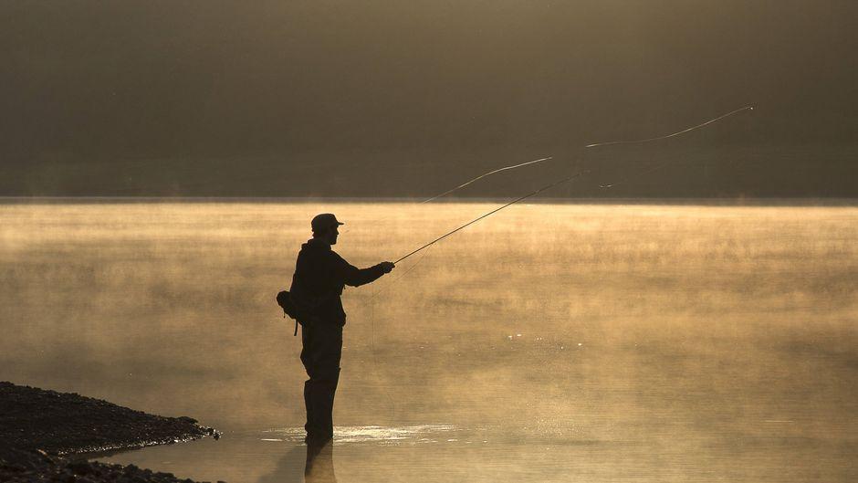 Angler steht im Wasser