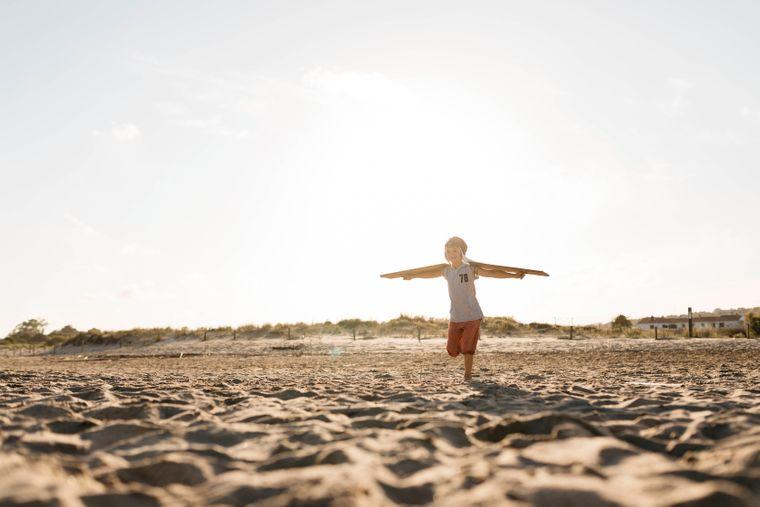 Ein Junge rennt mit Flügeln am Strand.