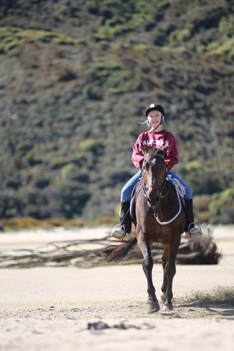 Reisereporterin Julia beim Ausritt am Strand in Neuseeland.