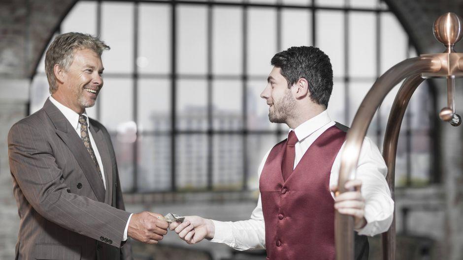 Ein Hotelgast gibt einem Mitarbeiter Trinkgeld.