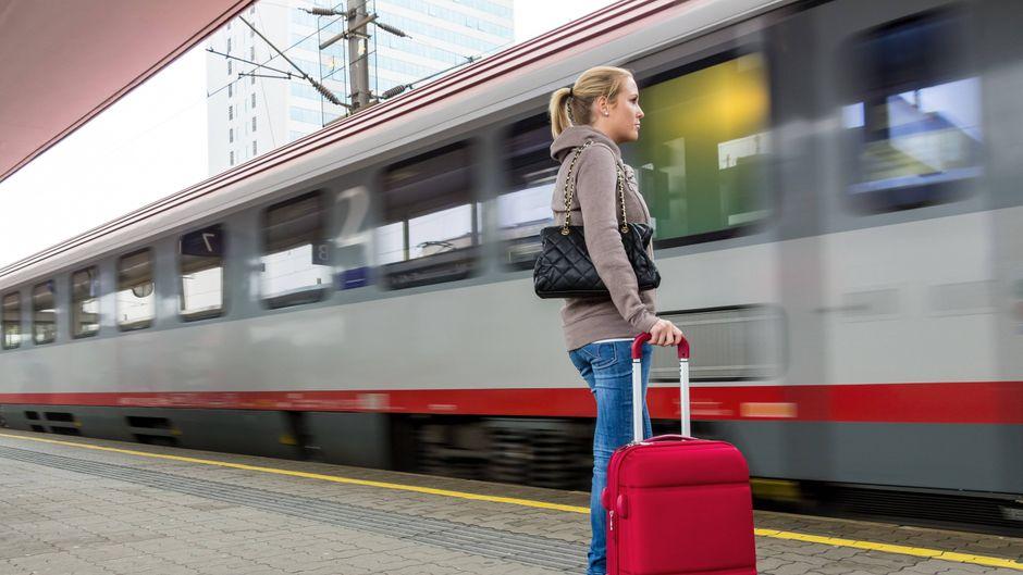 Eine junge Frau wartet auf einen Zug in einem Bahnhof.