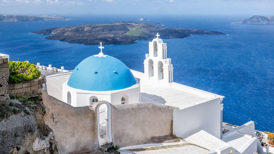Eine typische weiße Kirche mit blauem Dach strahlt mit dem herrlichen blauen Himmel auf Santorin um die Wette.