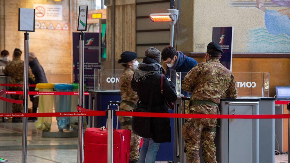 Militärmitarbeiter kontrollieren Reisende am Bahnhof von Mailand.