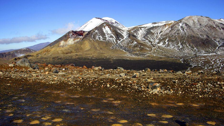 Vor den Bergen, deren Spitzen  mit Schnee bedeckt sind, liegt ein kleiner tiefblauer See. Drumherum ist  die Erde rostrot.