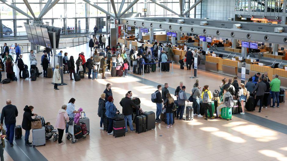 Passagiere warten in langen Schlangen vor den Check-in-Schaltern am Hamburg Airport.