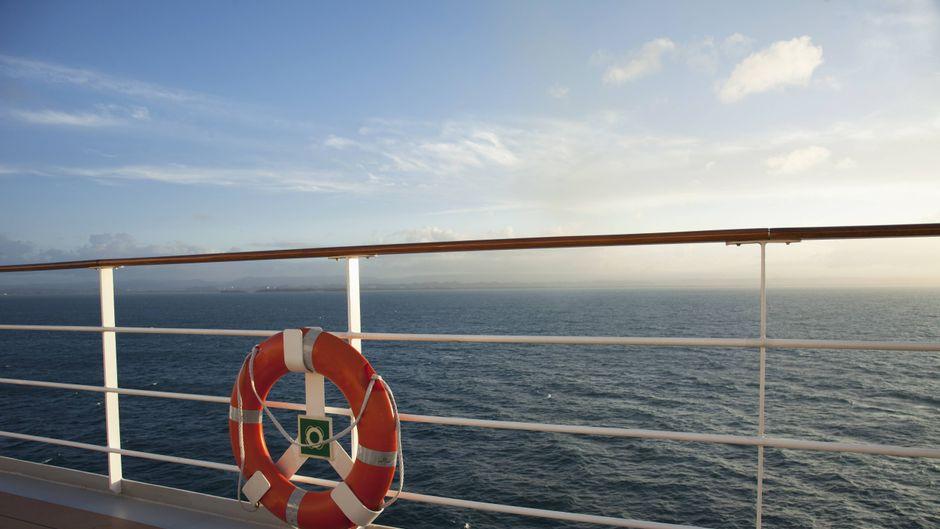 Blick vom Kreuzfahrtschiff: Im Vordergrund die Reling und ein Rettungsring.
