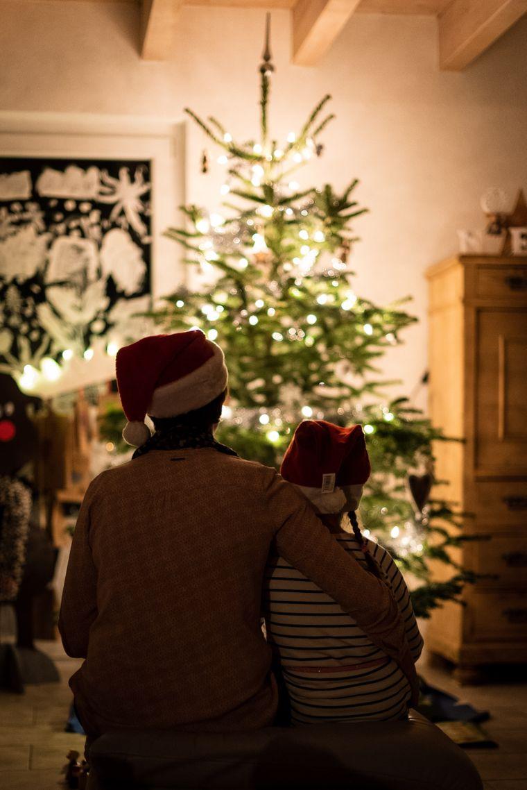 Familie vor Weihnachtsbaum.