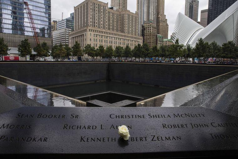 Eine Rose steckt in dem am Geländer des Denkmals ausgefrästen Namen eines Opfers der Anschläge auf das World Trade Center in New York City.