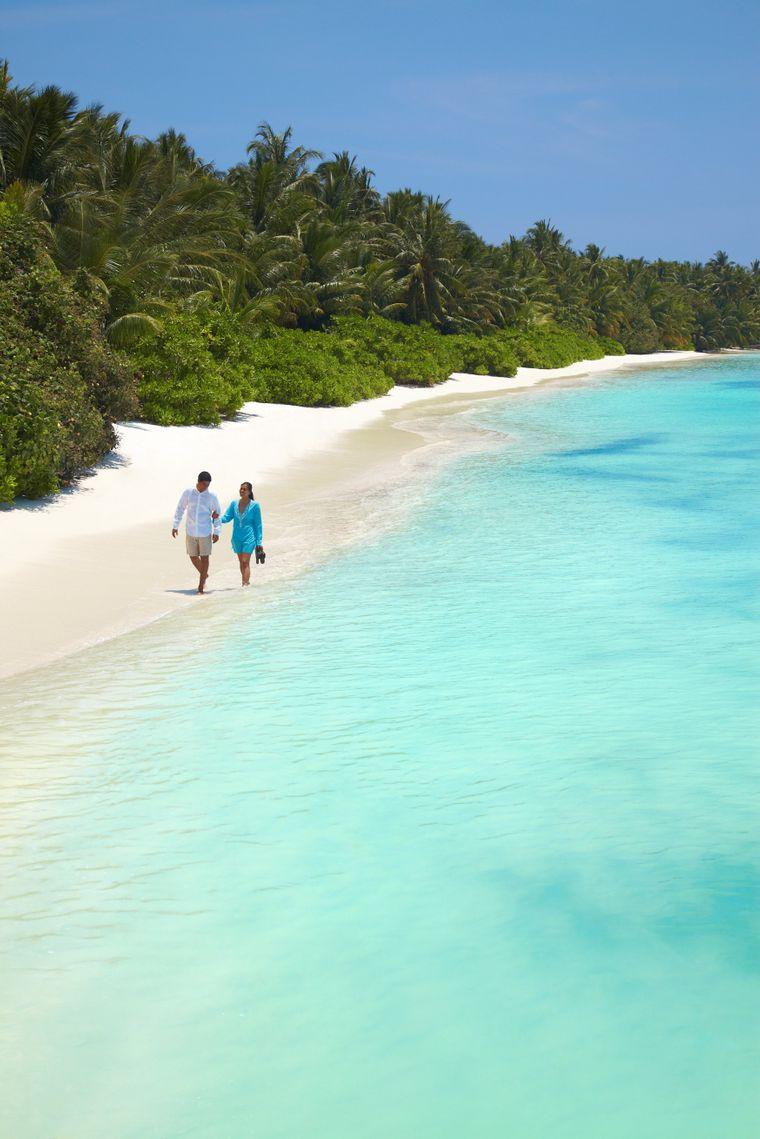 Zu Zweit den weißen Strand entlang spazieren.