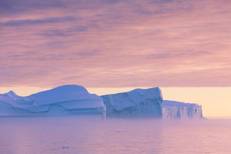 Sonnenaufgang über den Eisbergen Grönlands.