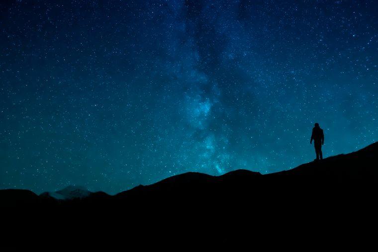 Ein Mann steht in Kanada unter freiem Sternenhimmel.