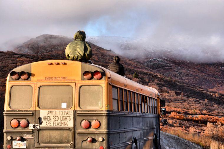 Zwei Jungs sitzen auf dem Schulbus in Alaska und schauen auf Berge.