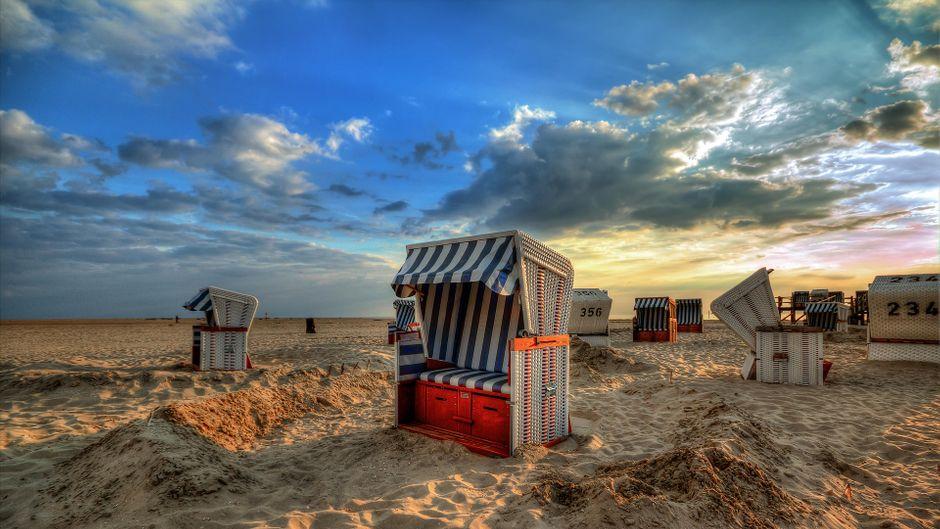 Strandkörbe am Strand mit Sonne und Wolken