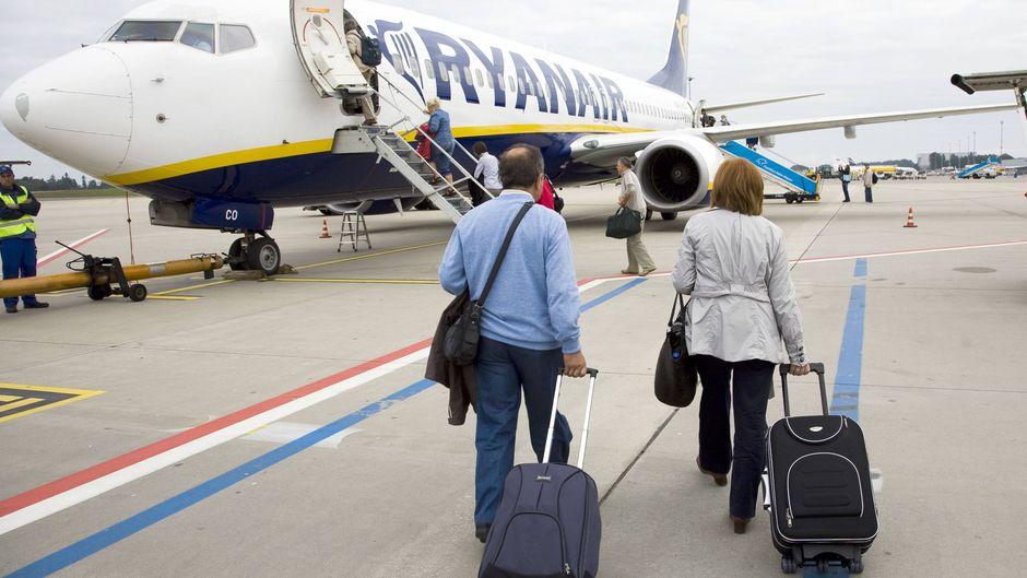Zwei Passagiere mit Handgepäck gehen auf Ryanair-Flugzeug zu.