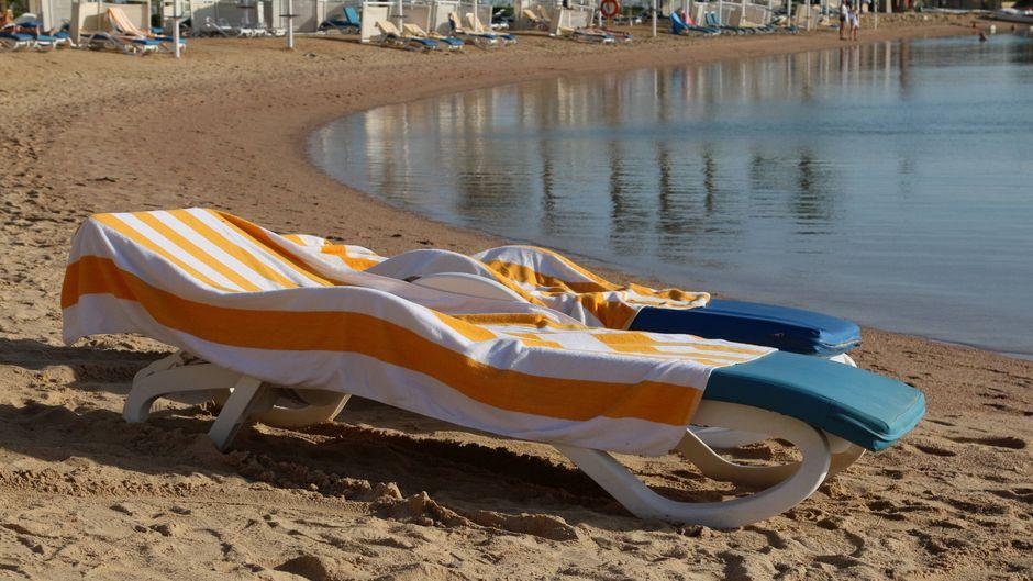 Handtücher bedecken zwei Sonnenliegen.