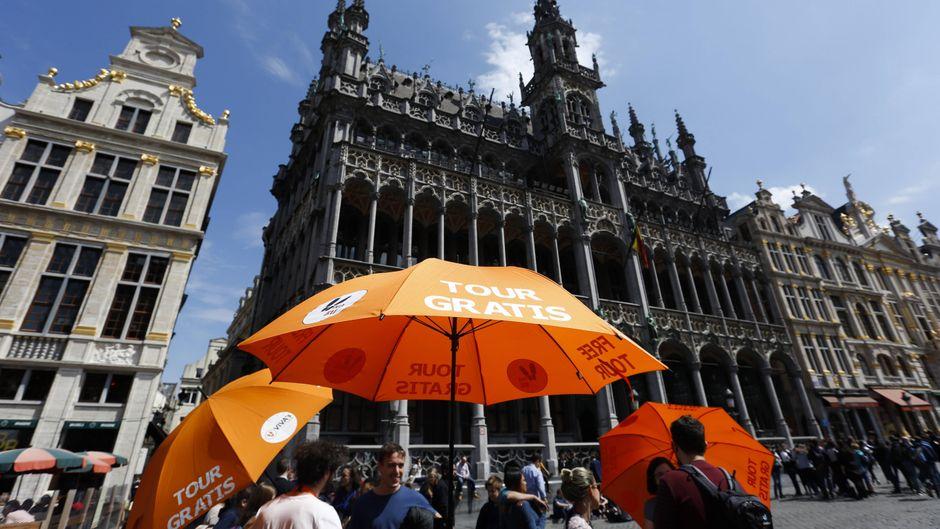 Ein Free-Tour-Guide hält in Brüssel einen Schirm in die Höhe.