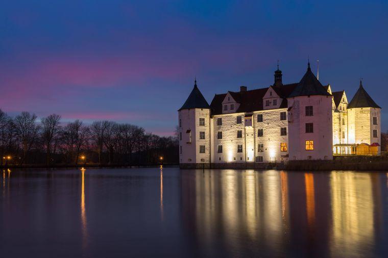 Zur blauen Stunde wird das Wasserschloss Glücksburg hell beleuchtet.